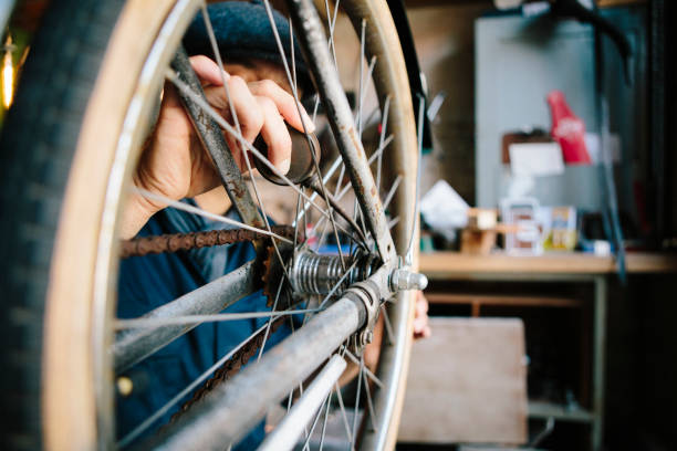 hobby mechanic in overall repairs a bicycle in his workshop stock photo