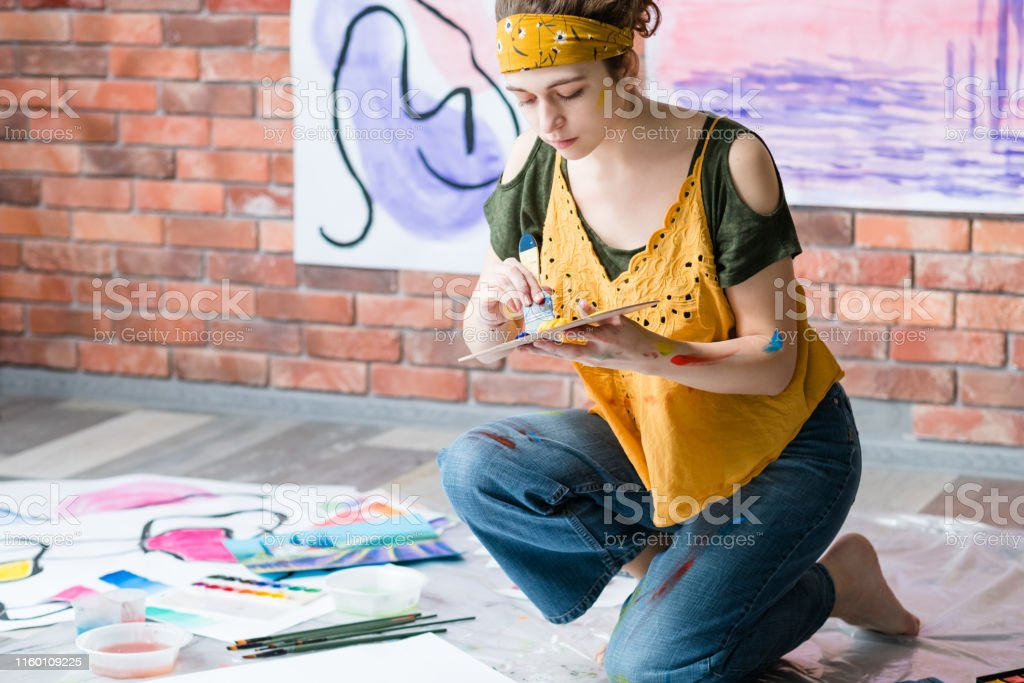 Hobby and recreation. Side view of lady sitting on floor, painting...