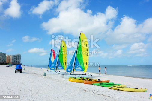 Marco Island, Florida, USA - July 7, 2013: A row of sea kayaks, paddle boards and Hobie catamarans rest on the beach awaiting use by guests of a nearby oceanside resort. People can be seen running and walking on the beach. Oceanside resort buildings are seen in the distance as well. The blue waters of the Gulf of Mexico are relatively calm along the shore.