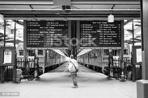 Hoboken, New Jersey, USA - April 11, 2016: A commuter looks at the train schedule board at Hoboken Terminal