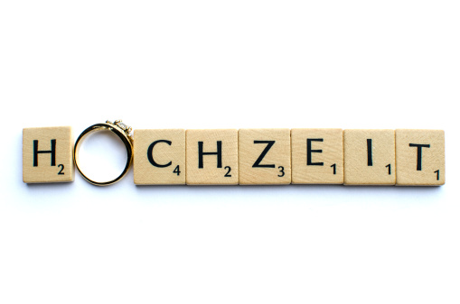 """""""Hochzeit"""" written with Scrabble tiles and an engagement ring"""