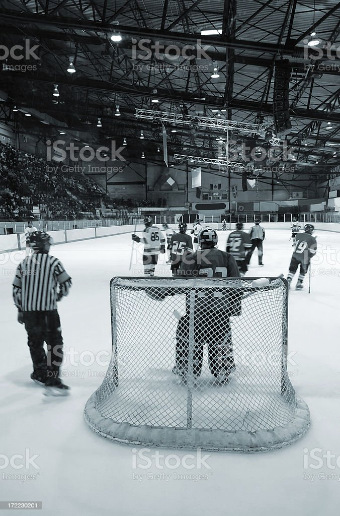 Hockey game view from behind one of the goalies royalty-free stock photo