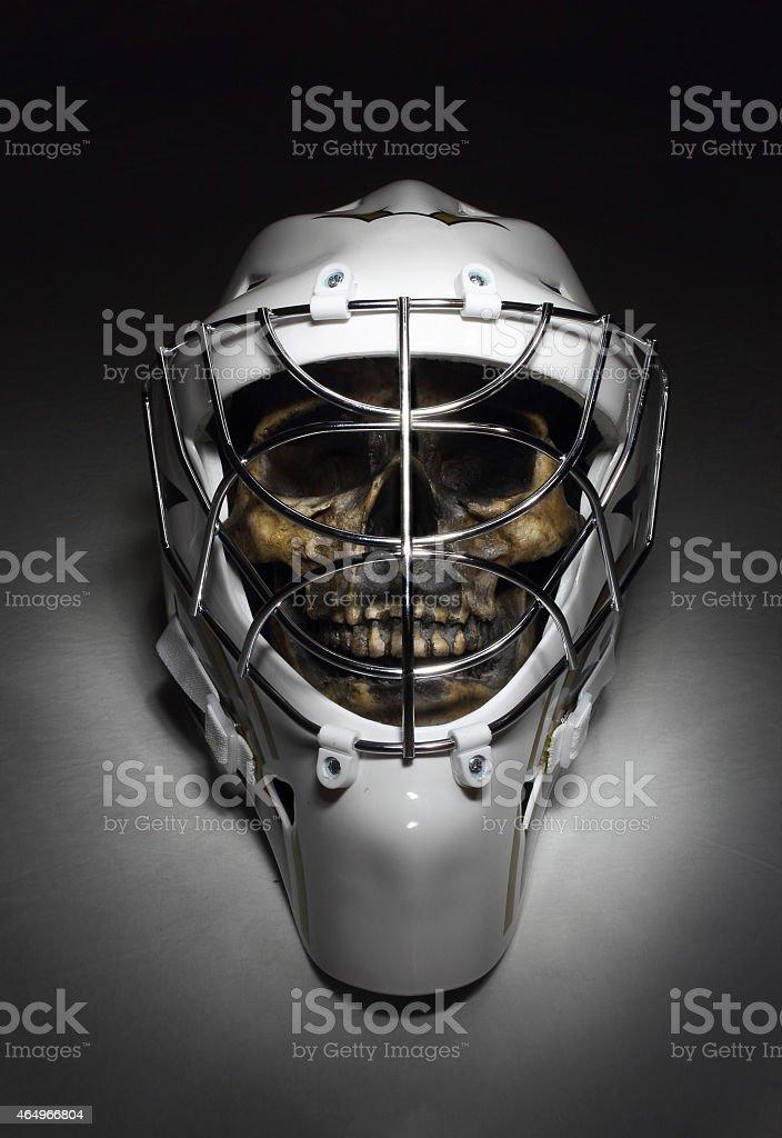 Hockey goaltender's mask worn by grinning skull. stock photo
