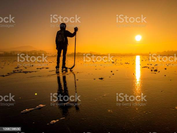 Photo of Hockey player on a frozen lake at sunset