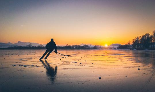 Hockey player skating on a frozen lake at sunset
