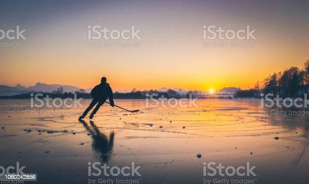 Photo of Hockey player skating on a frozen lake at sunset