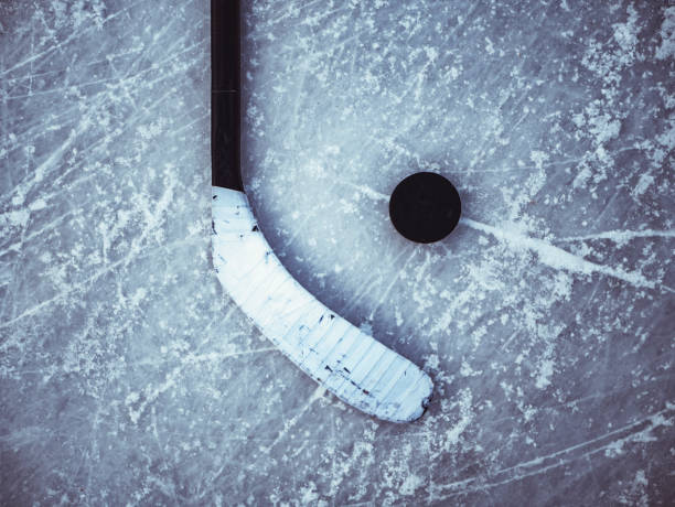 hockey puck and stick laying on the textured ice close up copyspace - hockey stock pictures, royalty-free photos & images
