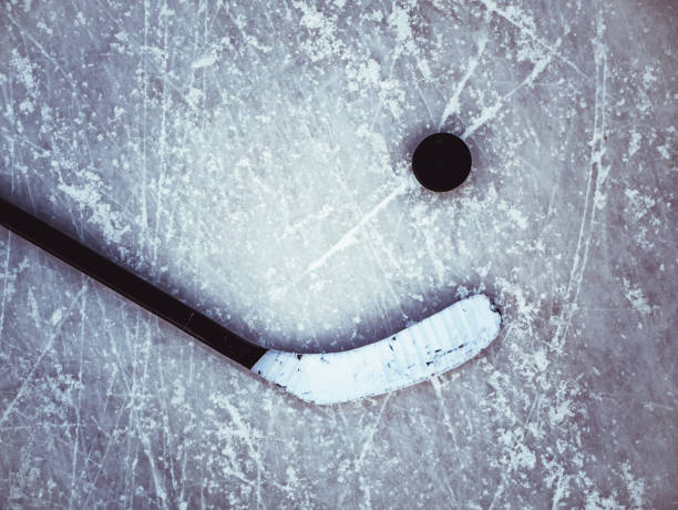 hockey puck and stick on the ice texture background - hockey stick stock pictures, royalty-free photos & images