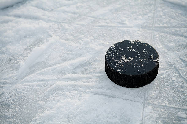 hockey puck on ice hockey rink - hockey stock pictures, royalty-free photos & images