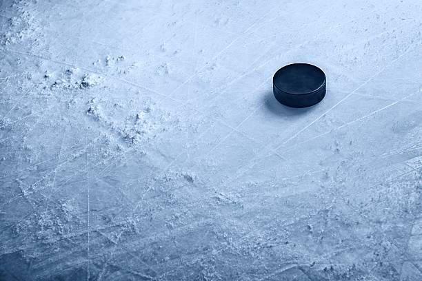 hockey puck on ice - hockey puck stock photos and pictures
