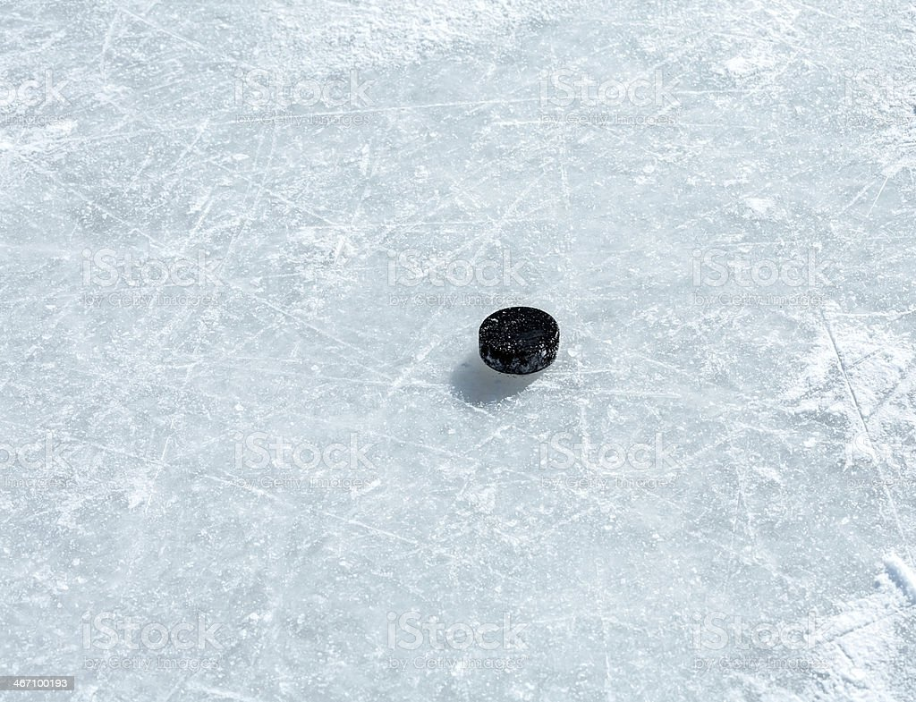 Hockey puck on ice rink stock photo