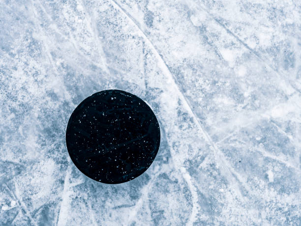 hockey puck on the ice and snow texture, copyspace and text - hockey puck stock photos and pictures