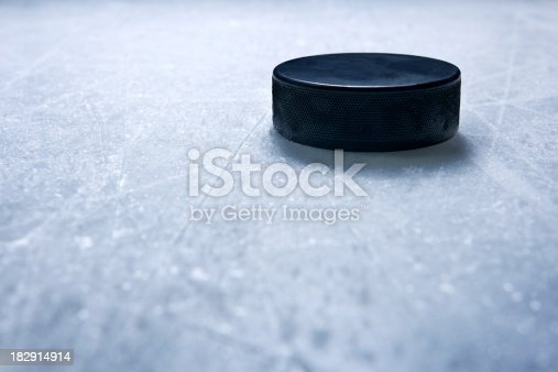 A hockey puck on ice textured by skate marks.Click on an