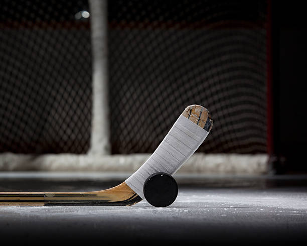 hockey puck, stick, and net (landscape) - hockey puck stock photos and pictures