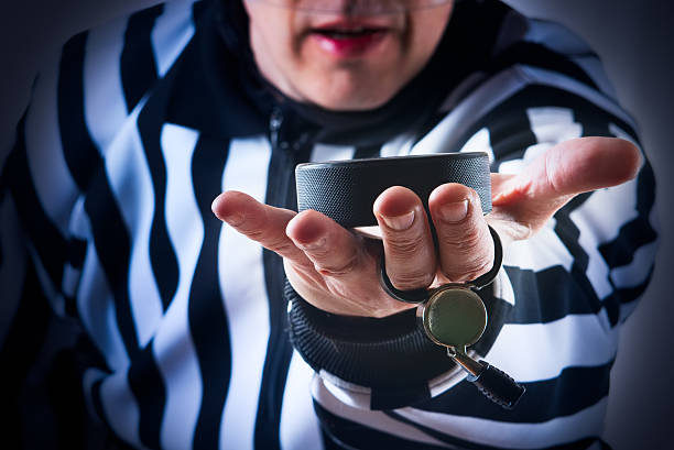 Hockey referee hold a puck Hockey referee hold a puck in his palm. Close view referee stock pictures, royalty-free photos & images