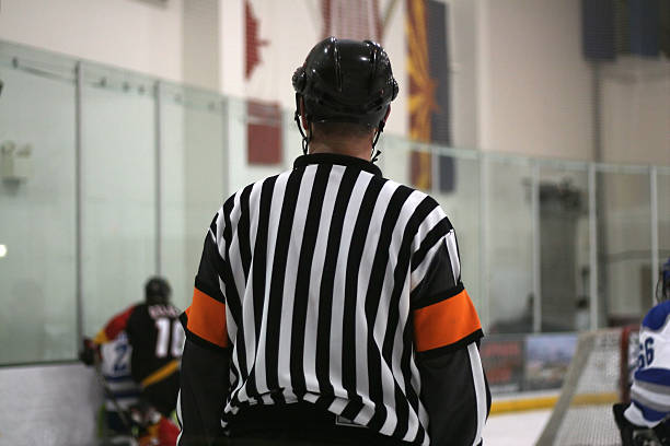 Hockey Referee (2) A hockey referee watches the action on the ice. referee stock pictures, royalty-free photos & images