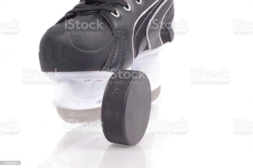 Hockey skates and puck on ice royalty-free stock photo