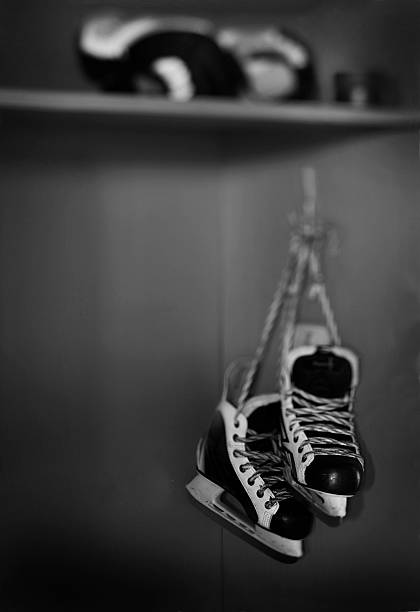 Hockey skates hanging in locker room stock photo