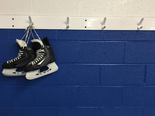 Hockey skates hanging on locker room stock photo