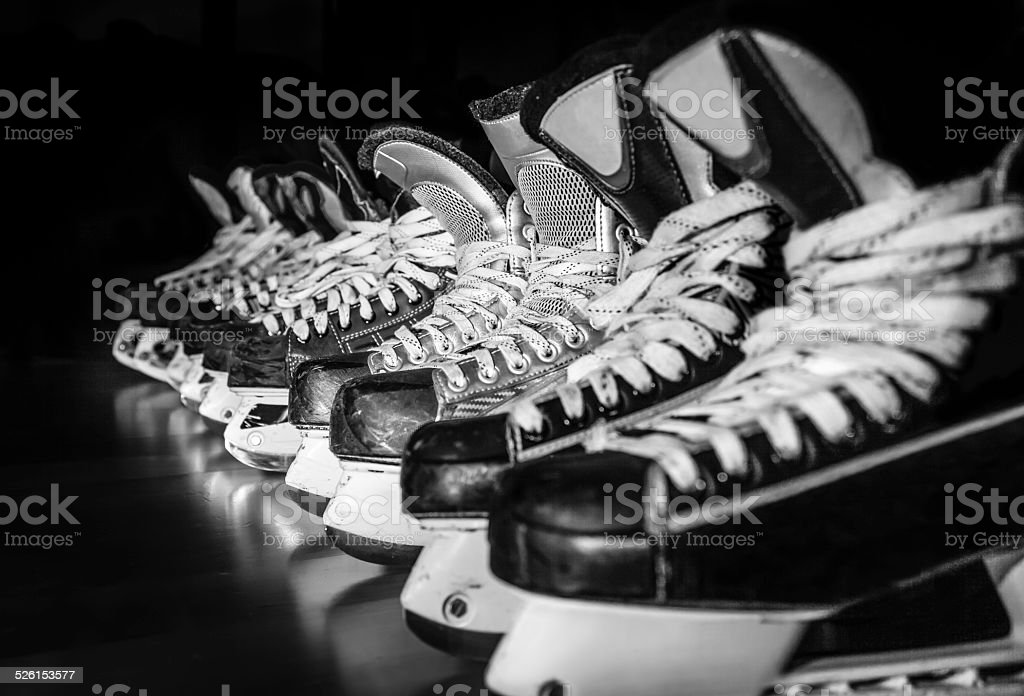 Hockey skates lined up in locker room stock photo