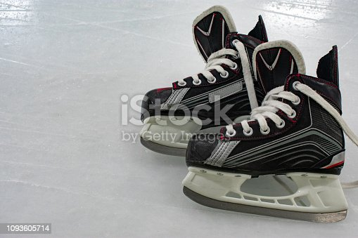 istock Hockey skates lying over ice rink with copy space 1093605714