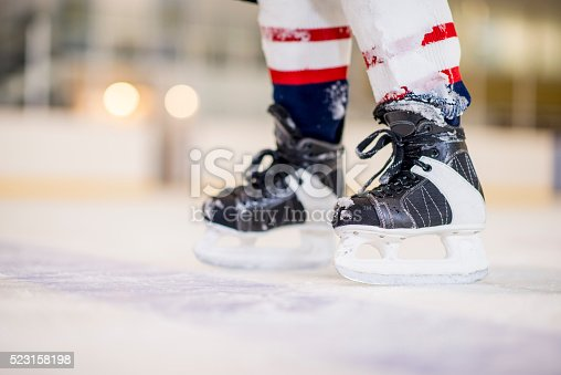 A picture of a man's hockey skates while standing on the ice skating rink.