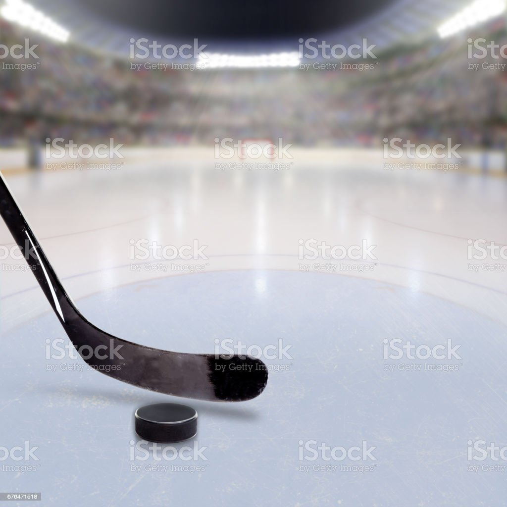Hockey Stick and Puck on Ice of Crowded Arena stock photo
