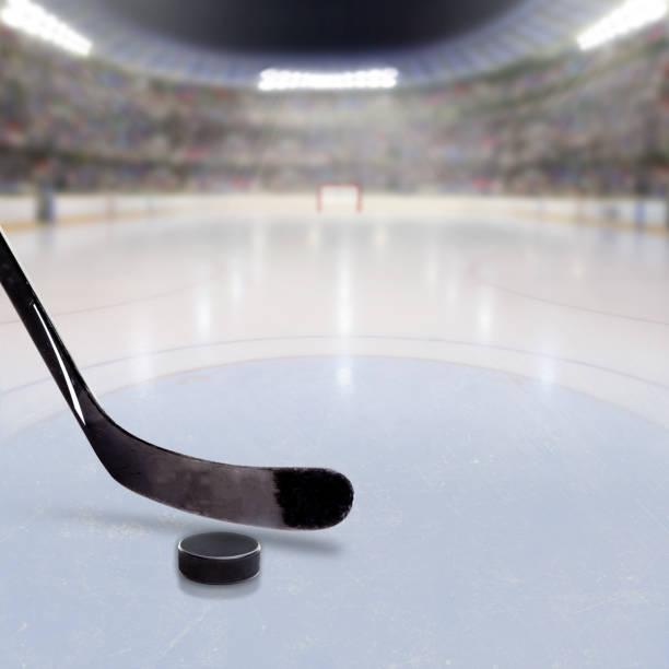 Palo de hockey y Puck en el hielo de la Arena llena de gente - foto de stock
