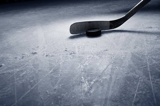Hockey Stick and Puck on Ice stock photo