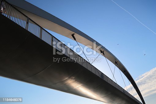 Abstract image of the Hoge Brug, or high bridge, in Maastricht, Netherlands, a steel arch bridge constructed for pedestrian and bicycle traffic to cross the Meuse River.  Image colors are primarily silver-gray and sky-blue with the bridge span crossing diagonally from upper left frame to lower right.  A bank of clouds fills the lower right frame in an otherwise clear blue sky.  A single jet trail crosses the upper right corner and several birds appear in mid-flight.  An unrecognizable lower torso and arm are obscured behind the bridge railing in the extreme upper left corner - just enough to offset pure abstraction and suggest the bridge's intended use.