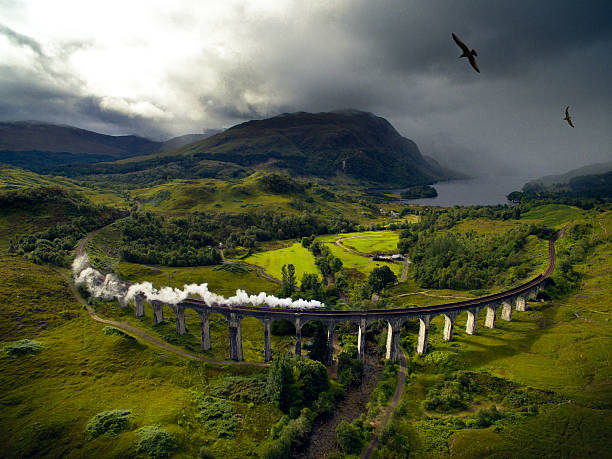 Hogwarts Express A steam train on a viaduct going through dramatic landscape to Hogwarts, school of Witchcraft and Wizardry scottish highlands stock pictures, royalty-free photos & images