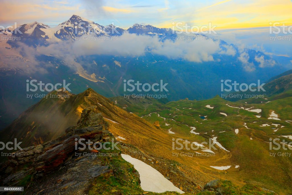 Hohe Tauern Snowcapped Austrian mountain range at gold colored sunrise - Tirol Alps dramatic cloudscape Sky and landscape and Grossglockner Massif stock photo