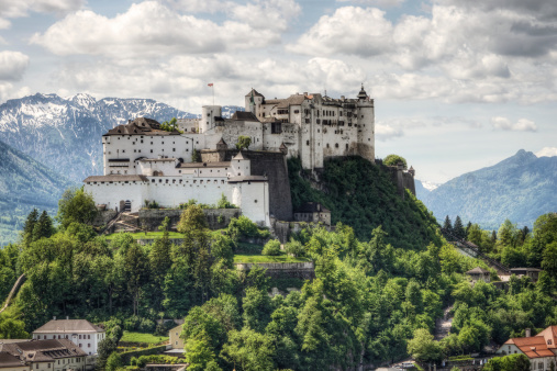 Salzburg, Austria: The Hohensalzburg Fortress in Salzburg Austria with Alps range rising in the distance. Built over several hundred years (from the 11th to 16th centures), it is one of the largest medieval castles in Europe with a length of 250 m (820 ft) and a width of 150 m (490 ft) and was added to the UNESCO list of world heritage sites 1996. Today it is one of the most recognized landmarks in central Europe.