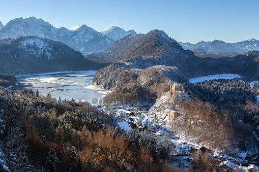 Hohenschwangau castle, village and Alpsee lake with the mountain range in the background