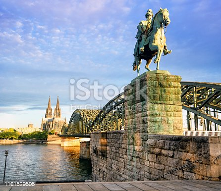 Kaiser Wilhelm Monument on the Hohenzollern Bridge at sunrise in Cologne, Germany. Composite photo