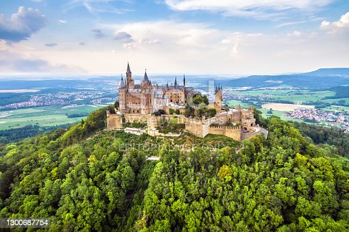 Hohenzollern Castle on mountain top, aerial view of old German burg in summer, Germany. This castle is famous landmark in Stuttgart vicinity. Swabian landscape with fairytale Gothic castle like palace.