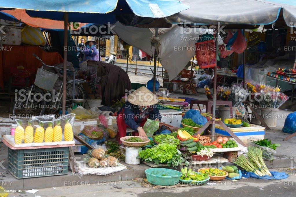 Hoi An, Vietnam - December 20th 2017. A market vendor sorts...