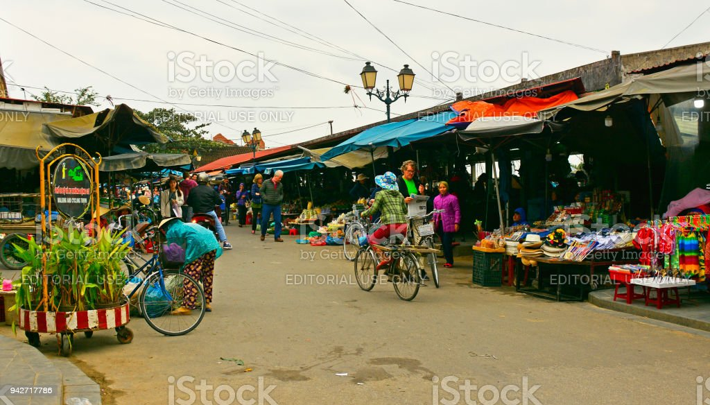 Hoi An, Vietnam - December 20th 2017. Market vendors sell food and...