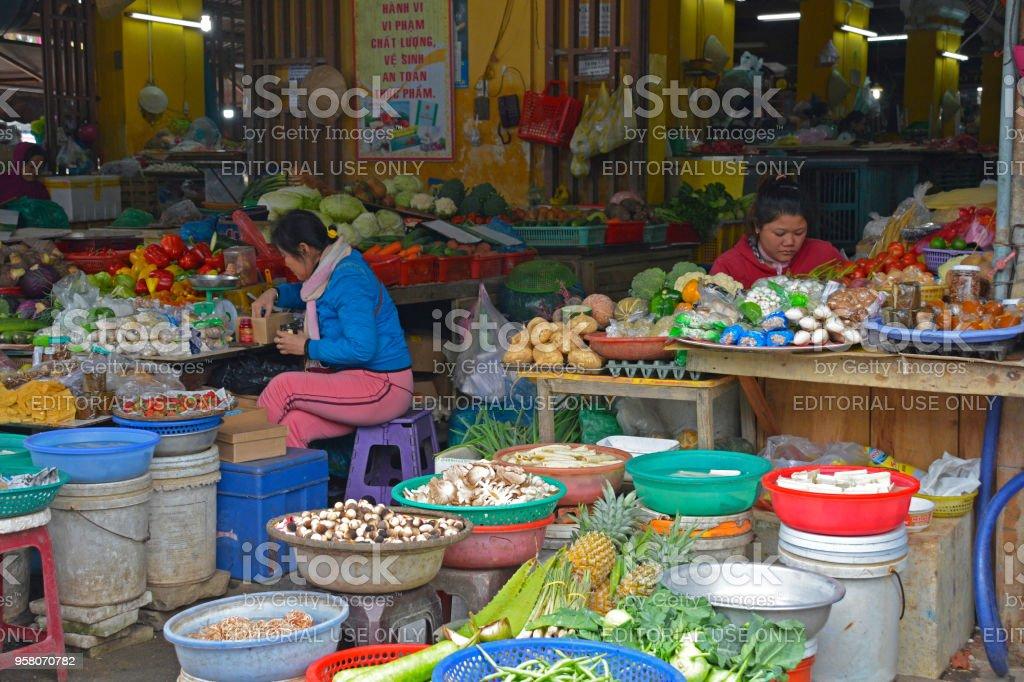 Hoi An, Vietnam - December 20th 2017. Market vendors wait for...