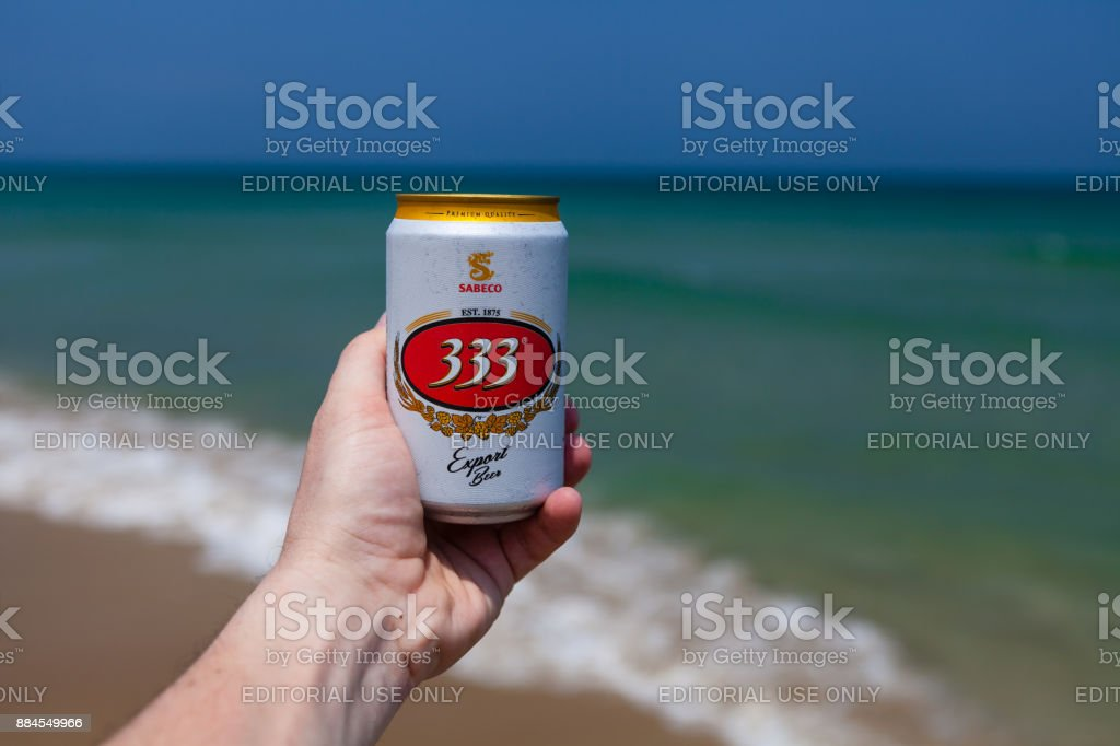 Hoi An, Vietnam - march 15 2017: hand holding can of cold 333 beer against emerald ocean and blue sky stock photo