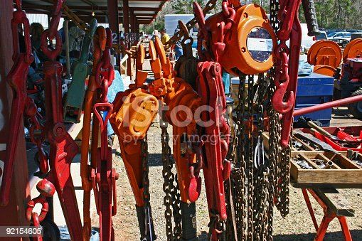 A collection of hoists and chains for sale at an outdoor flea market.
