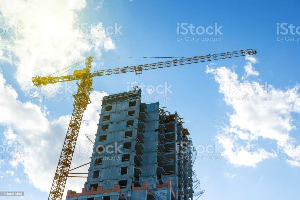 Hoisting crane working building construction on bright blue sky and big cloud with sun flare background. stock photo