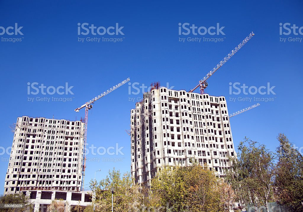 Hoisting tower cranes and top of construction buildings stock photo