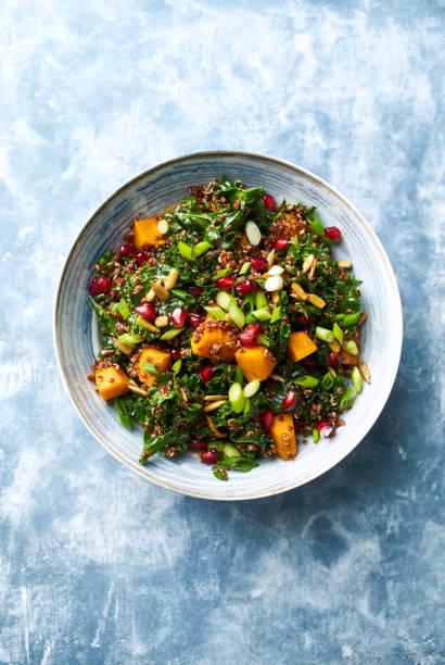 Hokkaido Kürbis und Quinoa-Salat mit Grünkohl, Granatapfel, Frühlingszwiebeln und gerösteten Sonnenblumenkernen. Gesunde hausgemachte Lebensmittel. Veganes Essen – Foto