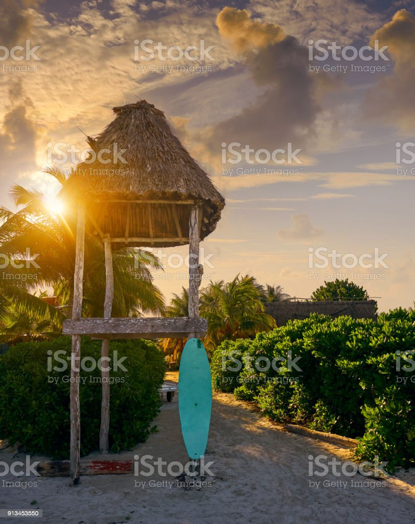 Holbox Island baywatch tower and surf board stock photo