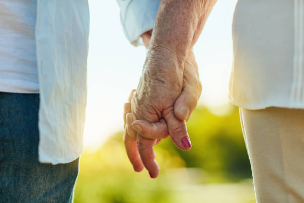 Hold my hand and let's make it last Cropped shot of a senior couple holding hands in a park falling in love stock pictures, royalty-free photos & images