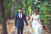Bride and groom walking through the park together