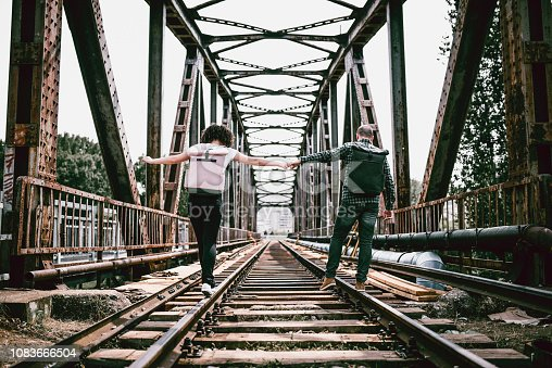 Cute Young Couple Holding Hands While Walking On Railway Bridge