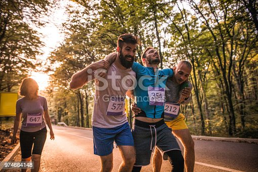 Male athletes helping their injured friend during a marathon race on the road through nature.