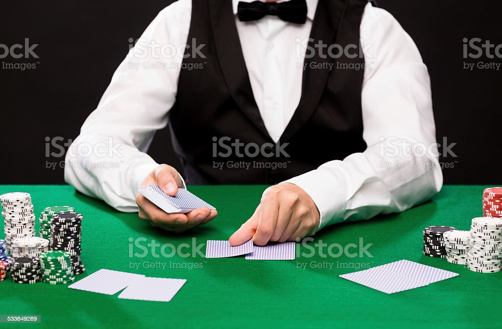 holdem dealer with playing cards and casino chips stock photo